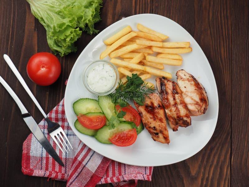 Geroosterde lapjes vlees, frieten en plantaardige salade stock fotografie