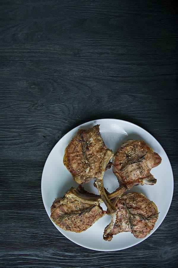 Geroosterde lapjes vlees van varkensvleesribben met kruiden en kruiden Weergeven over de donkere houten achtergrond Ruimte voor t royalty-vrije stock fotografie