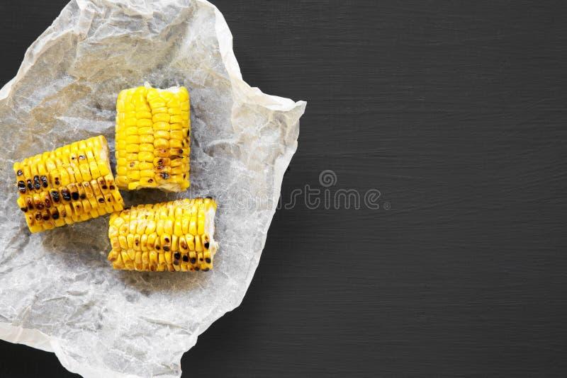 Geroosterde maïskolven ove zwarte achtergrond, hoogste mening De zomervoedsel Van hierboven, vlak leg royalty-vrije stock foto's