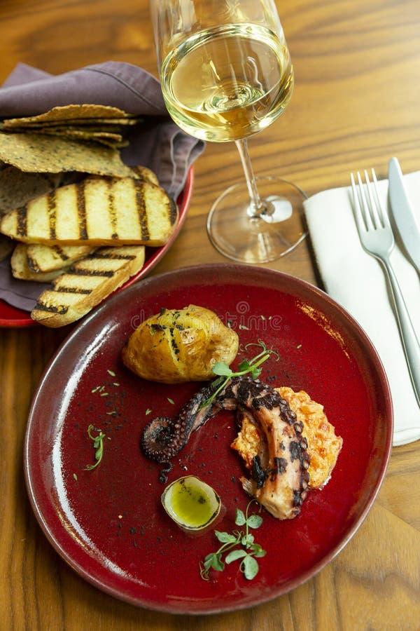 Geroosterde octopus op een rode plaat in een restaurant Prachtig verfraaid diner met witte wijn royalty-vrije stock afbeeldingen