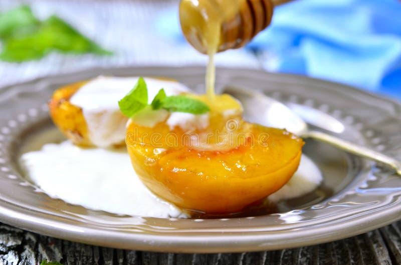 Geroosterde perzik met yoghurt en honing stock foto