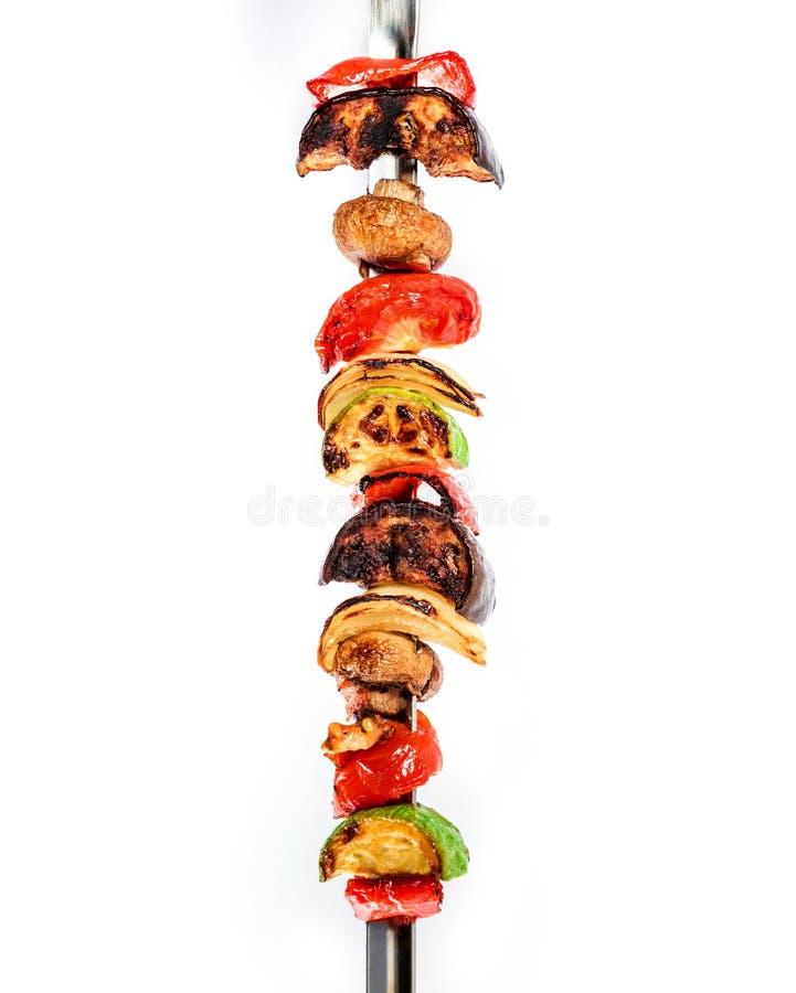 Geroosterde plantaardige kebabs op vleespennen met kersentomaat, peper, paddestoelen, pompoen en ui op witte achtergrond stock fotografie
