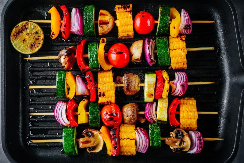 Geroosterde plantaardige vleespennen met suikermaïs, paprika, courgette, ui op een grillpan stock foto's
