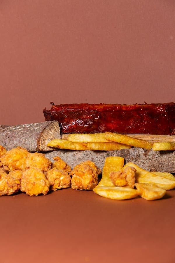 Geroosterde ribben met knapperige kip en gebraden gebraden gerechten tegen bruine achtergrond royalty-vrije stock foto's