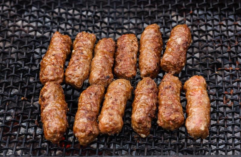 Geroosterde Roemeense vleesbroodjes op barbecuenet - mititei, mici royalty-vrije stock afbeelding