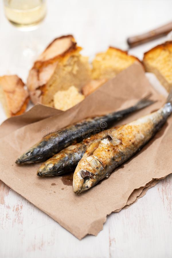 Geroosterde sardines met cornbread op papier stock fotografie