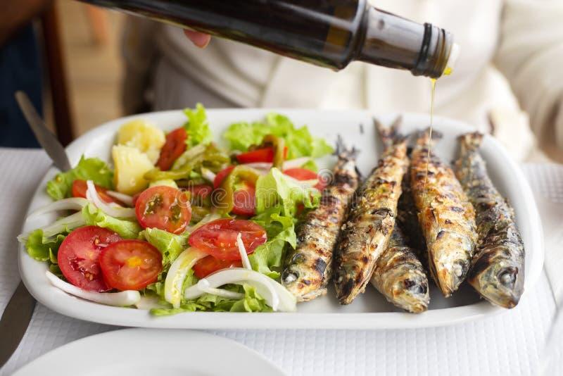 Geroosterde sardines met salade en olijfolie op witte schotel royalty-vrije stock foto's