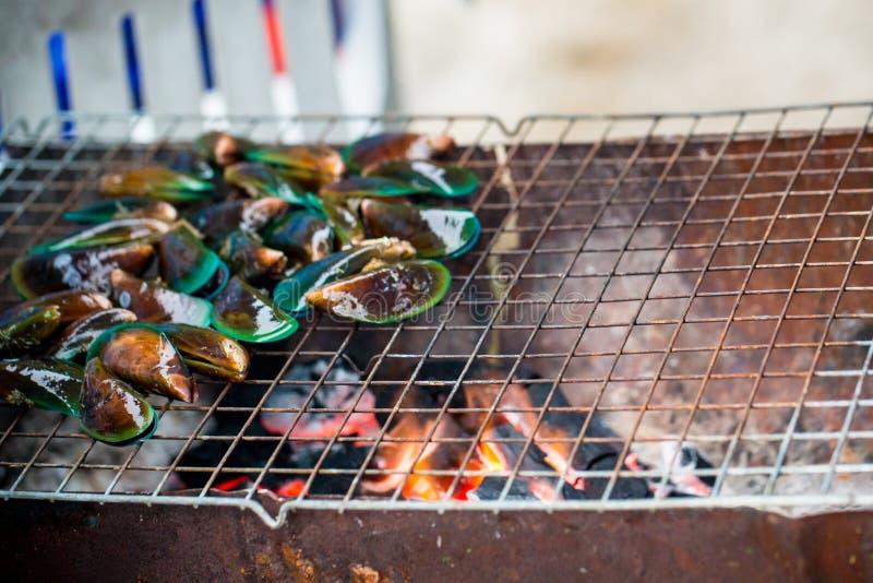 Geroosterde slakken op fornuistraliewerk, kokende barbecuezeevruchten met kruidige saus stock foto