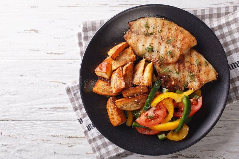 Geroosterde Tilapia filet en aardappelwiggen, vers saladeclose-up royalty-vrije stock fotografie