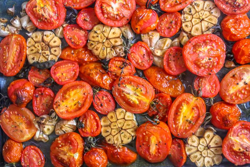 Geroosterde tomaten, knoflook en basilicumbladeren met thyme en olijfolie stock afbeeldingen