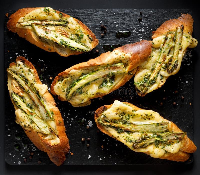 Geroosterde toosts, bruschetta met toevoeging van gesmolten kaas, groene asperge, olijfolie en kruiden op een zwarte achtergrond, stock foto's