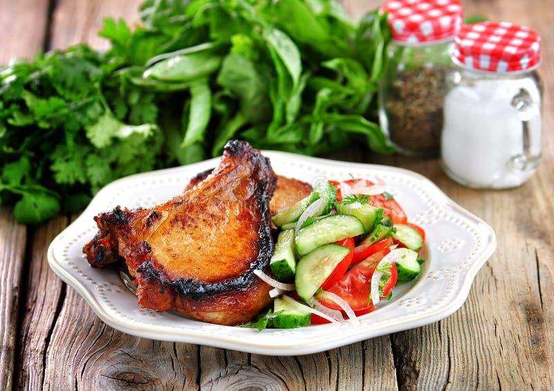 Geroosterde Varkenskotelet met salade van tomaten, komkommers, uien, peterselie en olijfolie stock afbeelding