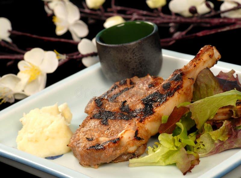 Geroosterde varkenskoteletten met fijngestampte aardappels en salade royalty-vrije stock foto