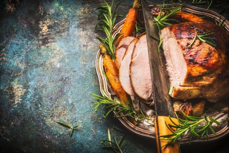 Geroosterde varkensvleesham met van het keukenmes en braadstuk groenten op donkere rustieke achtergrond royalty-vrije stock foto