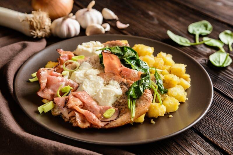 Geroosterde varkensvleeskoteletten met bacon, kaas, spinazie en aardappels royalty-vrije stock afbeeldingen