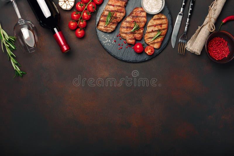 Geroosterde varkensvleeslapjes vlees op steen met fles van wijn, wijnglas, mes en vork op roestige achtergrond royalty-vrije stock afbeelding