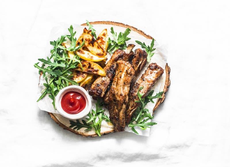 Geroosterde varkensvleesribben en frieten op houten raad op lichte achtergrond Heerlijke lunch, voorgerechten, tapas stock afbeelding