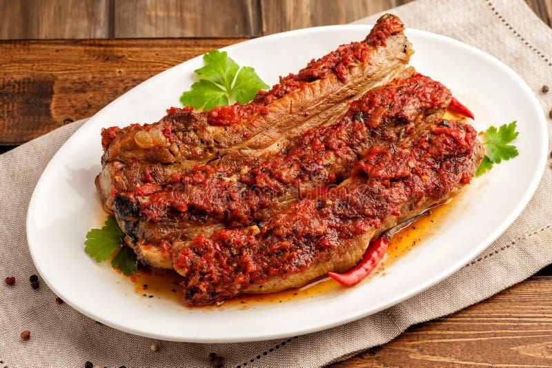 Geroosterde varkensvleesribben in kruidige saus met tomaten stock afbeeldingen