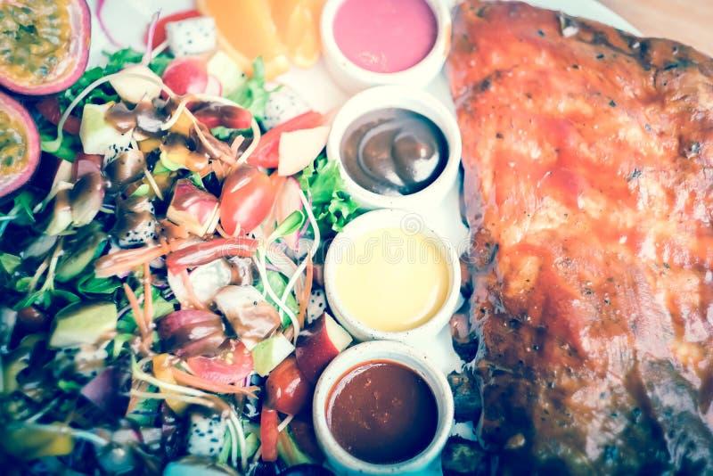 Geroosterde varkensvleesribben met barbecuesaus en fruitsalade stock foto's