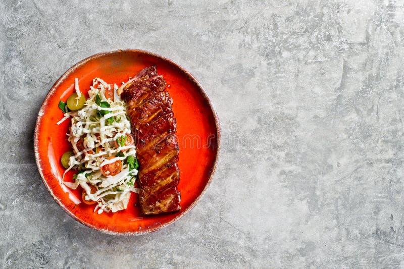Geroosterde varkensvleesribben met een bijgerecht van groene salade Grijze achtergrond, hoogste mening, ruimte voor tekst stock fotografie