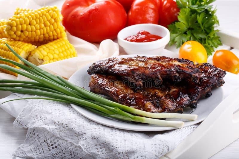 Geroosterde varkensvleesribben Vleesbbq ribben die met saus en verse groenten worden gediend stock foto's
