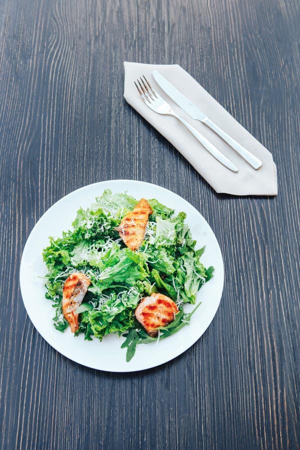 Geroosterde vissen en verse groene salade op een witte plaat Houten achtergrond royalty-vrije stock foto