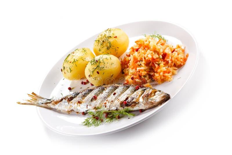Geroosterde vissen met aardappels stock fotografie