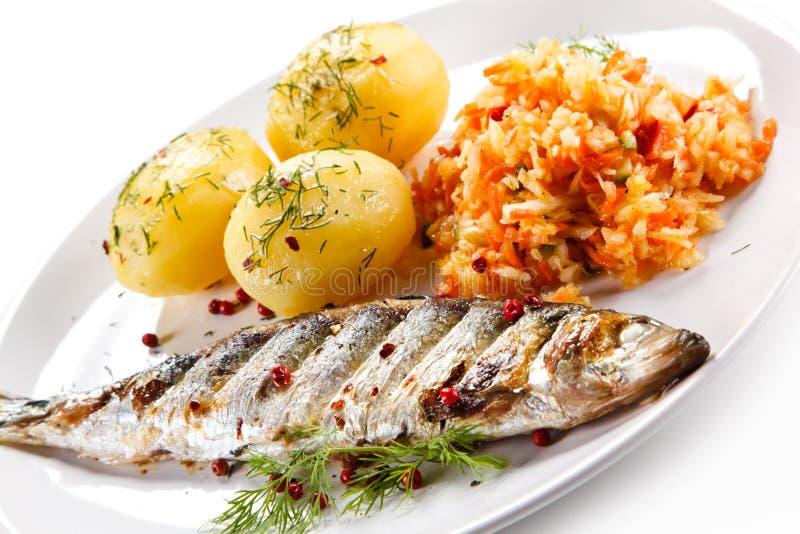 Geroosterde vissen met aardappels stock afbeelding