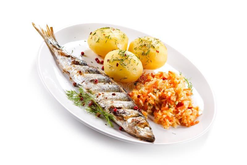 Geroosterde vissen met aardappels en plantaardige salade stock afbeeldingen