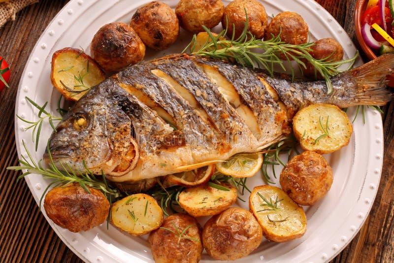 Geroosterde vissen met geroosterde aardappels en groenten op de plaat stock foto's