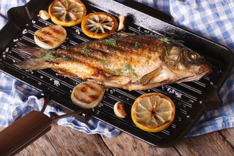 Geroosterde vissenkarper met citroen op een horizontale pangrill, stock fotografie