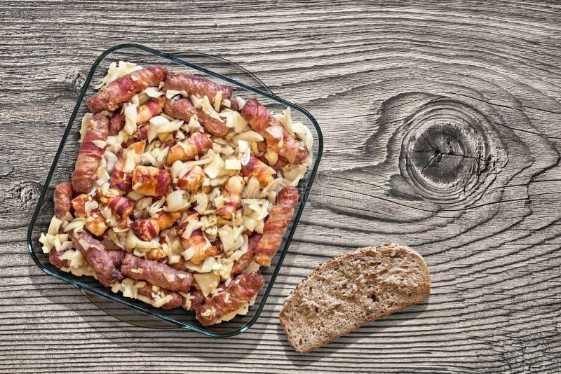 Geroosterde Vleesbroden Cevapcici die in Bacon en het Baconbroodjes van het Kippenvlees met Ui in de Lijst van Pan Set On Old Woo royalty-vrije stock afbeeldingen