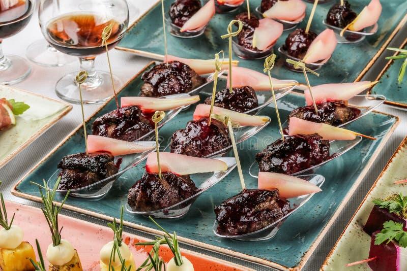 Geroosterde vleesfilet canapes met gebakken peer en bessensaus in lepel op banketlijst Cateringsvoedsel, voorgerechtschotel en sn royalty-vrije stock foto's