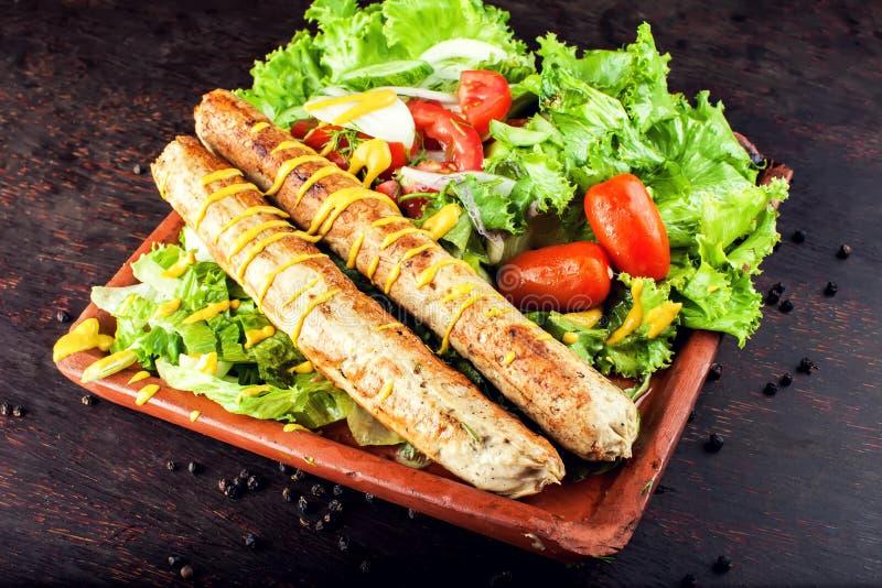 Geroosterde worst met groenten en mosterd op houten raad stock foto's