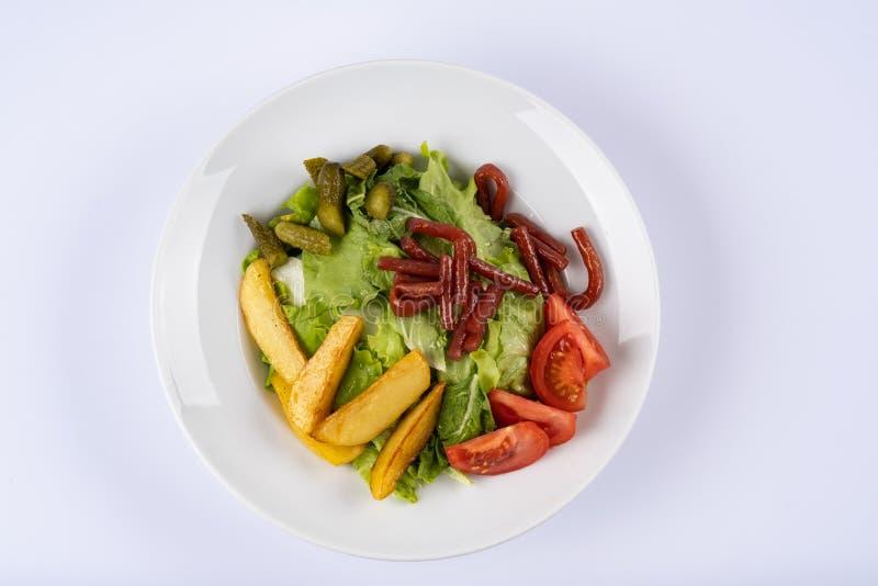 Geroosterde worsten, aardappelen in de schil en groenten op witte plaat royalty-vrije stock afbeelding