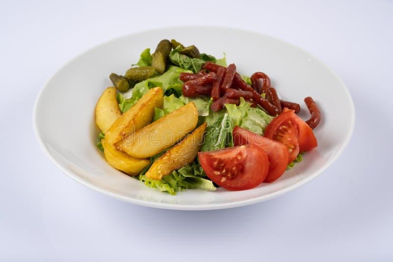 Geroosterde worsten, aardappelen in de schil en groenten op witte plaat stock afbeelding