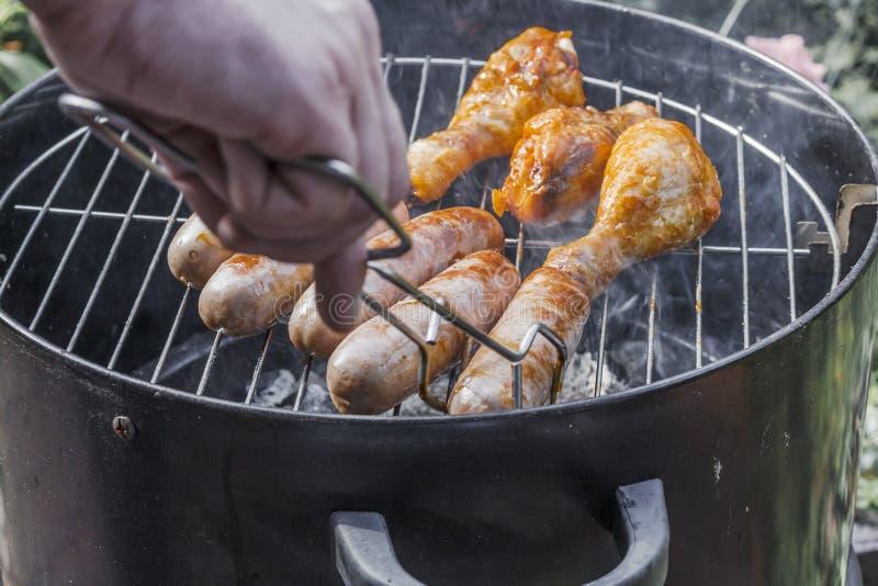 Geroosterde worsten en kippenbenen op de grill Heerlijk smakelijk sappig braadstukvlees Kokend voedsel openlucht proces om te kok royalty-vrije stock afbeelding