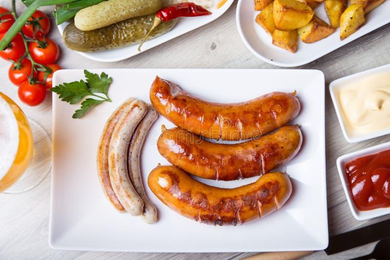 Geroosterde worsten met aardappels, komkommers en zuurkool, met twee sausen royalty-vrije stock afbeeldingen