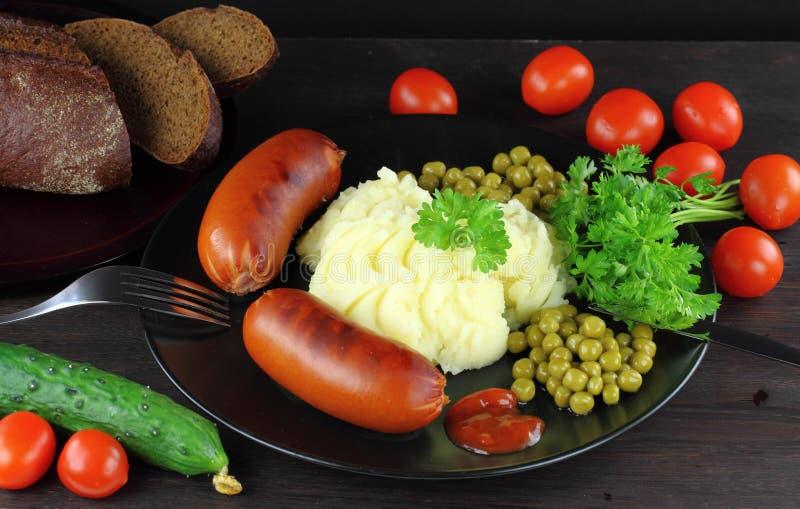 Geroosterde worsten met fijngestampte aardappel stock afbeeldingen