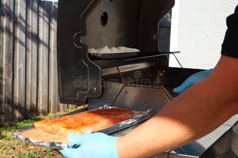 Geroosterde zalm op de vlammende grill Verse ruwe zalmfilet op houten die raad in folie het koken bij de grill wordt verpakt royalty-vrije stock foto