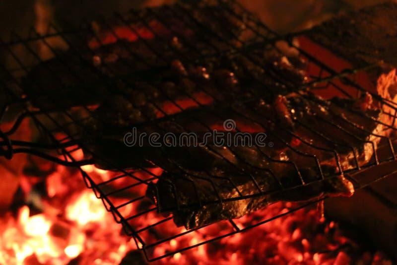 Geroosterde zalmlapjes vlees op een grill De grill van de brandvlam Restaurant en tuinkeuken stock foto's