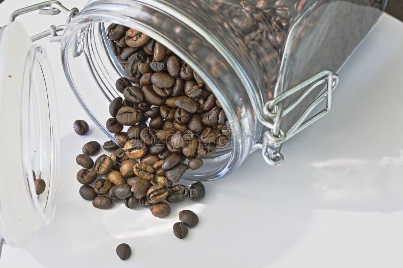 Geroosterde zwarte die koffiebonen van een kruik worden gemorst royalty-vrije stock afbeelding