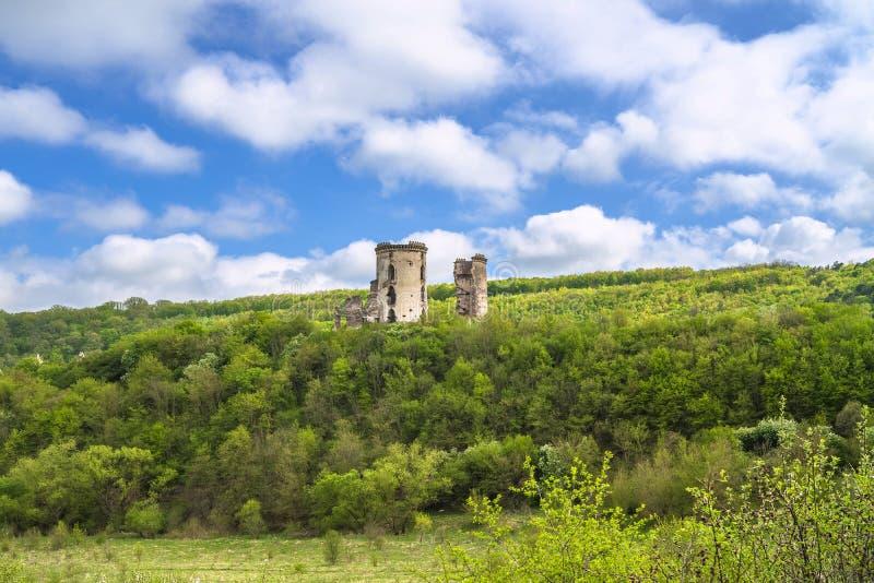Geruïneerd Chervonohrad-Kasteel Ruïnes van torens onder het bergbos royalty-vrije stock afbeelding