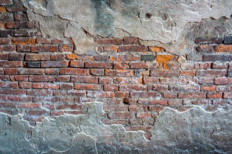 Geruïneerd geheel en gebroken bakstenen muur met barstend cement stock foto
