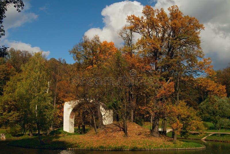 Geruïneerde boog op eiland in park stock foto