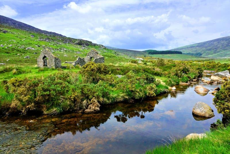 Geruïneerde mijnbouw langs een kreek in de Bergen Nationaal Park van Wicklow, Ierland stock fotografie