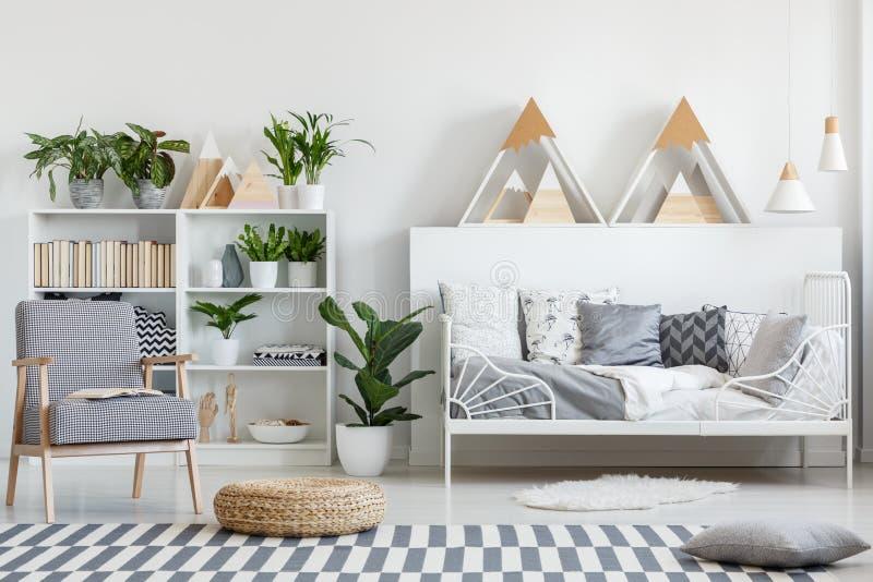 Geruite leunstoel, houten bergdecoratie en installaties in een wit, natuurlijk slaapkamerbinnenland voor een tiener stock foto's