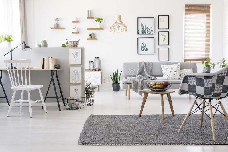 Geruite, modieuze stoel op een grijze deken in ruim, scandinavi royalty-vrije stock afbeelding