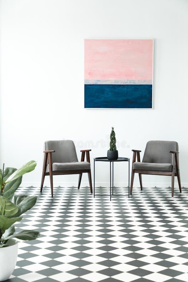 Geruite vloer met een installatie in een halbinnenland met armcha twee royalty-vrije stock afbeeldingen