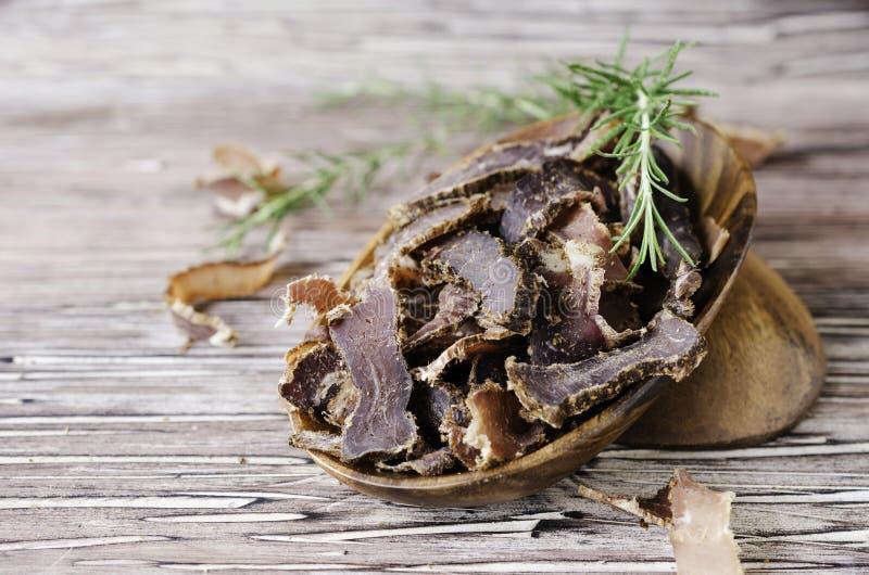 Gerukt vlees, koe, herten, wilde dier of biltong in houten kommen op een rustieke lijst royalty-vrije stock foto's
